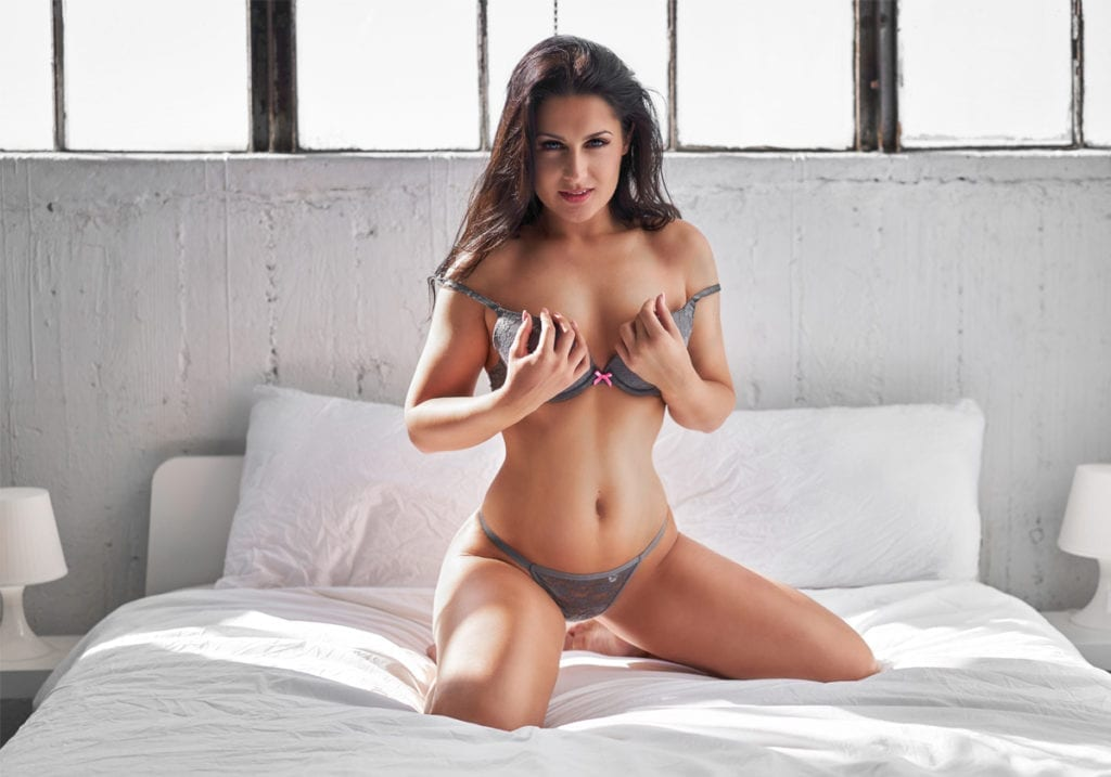 Woman wearing gray lingerie on photoshoot studio bed