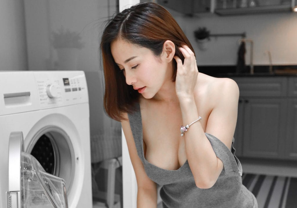 Woman doing laundry with cleavage showing