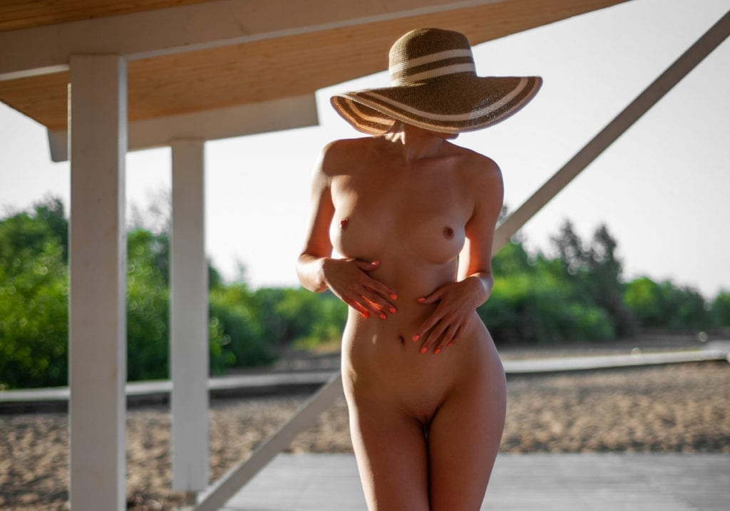 Woman nude outdoors on patio in private location